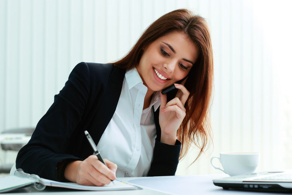 Young happy businesswoman talking on the phone and writing notes in office-1
